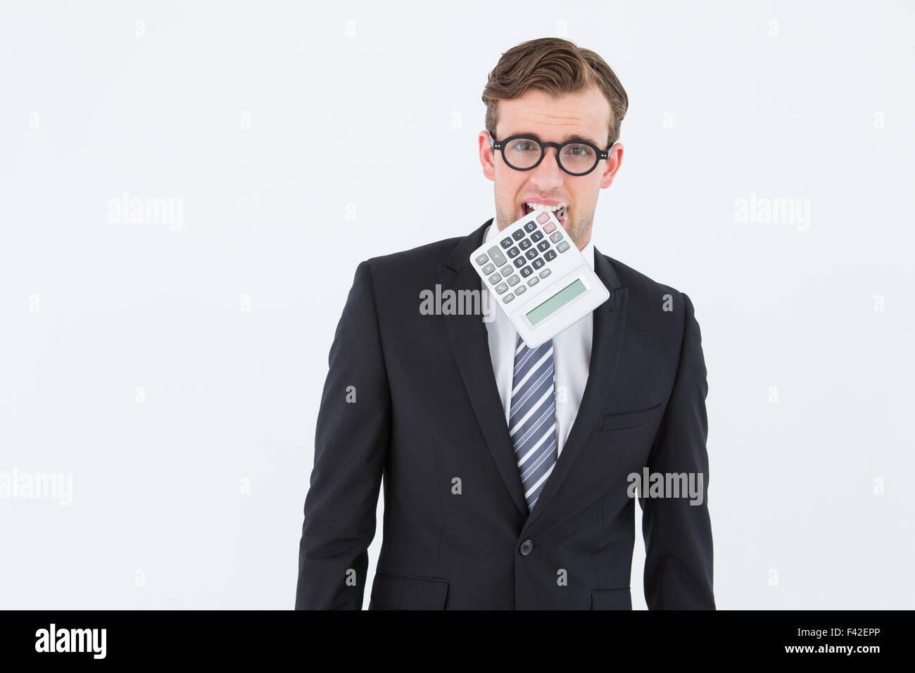 Geeky businessman biting calculator - Stock Image