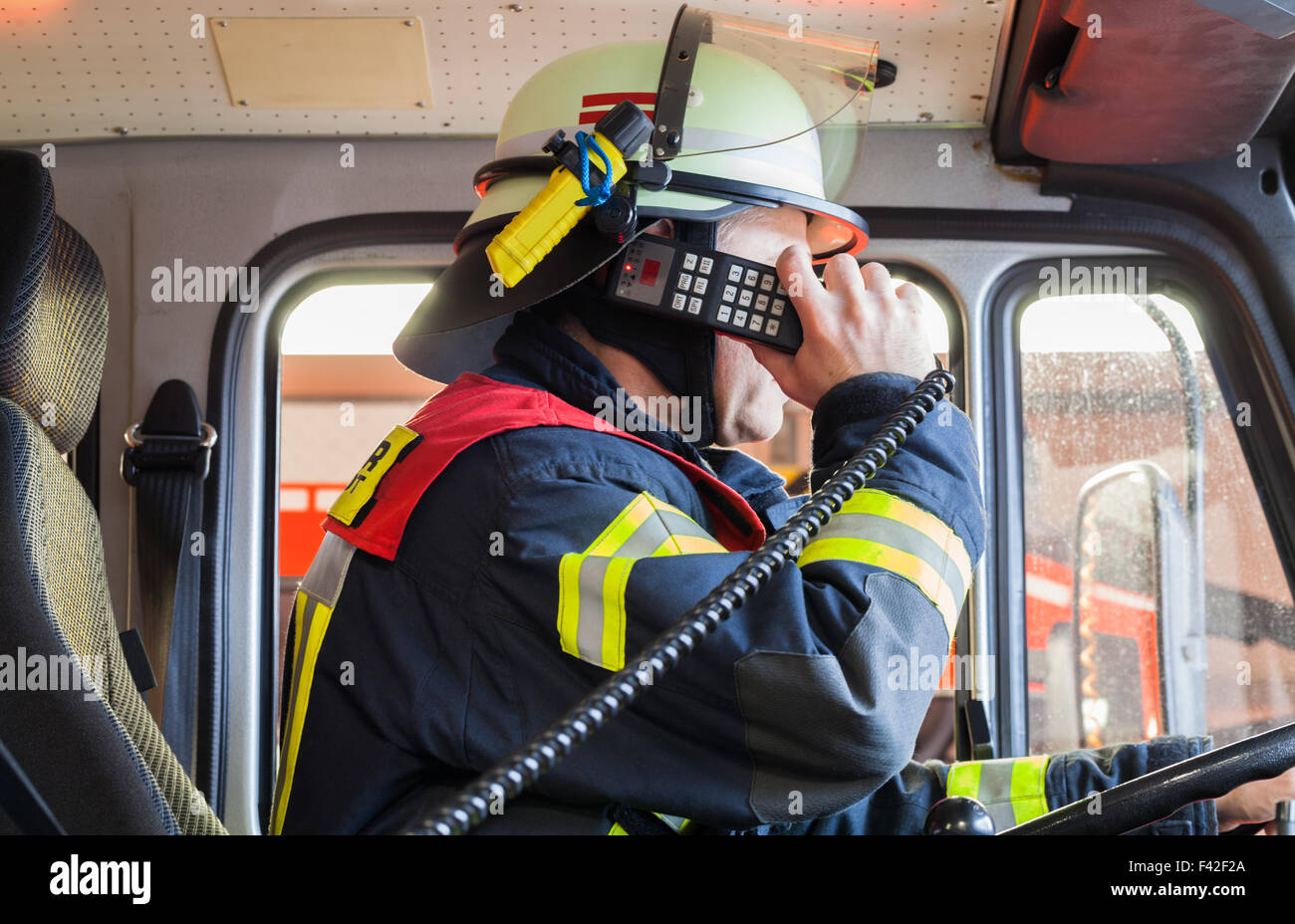 Fireman in action vehicle with radio - Stock Image