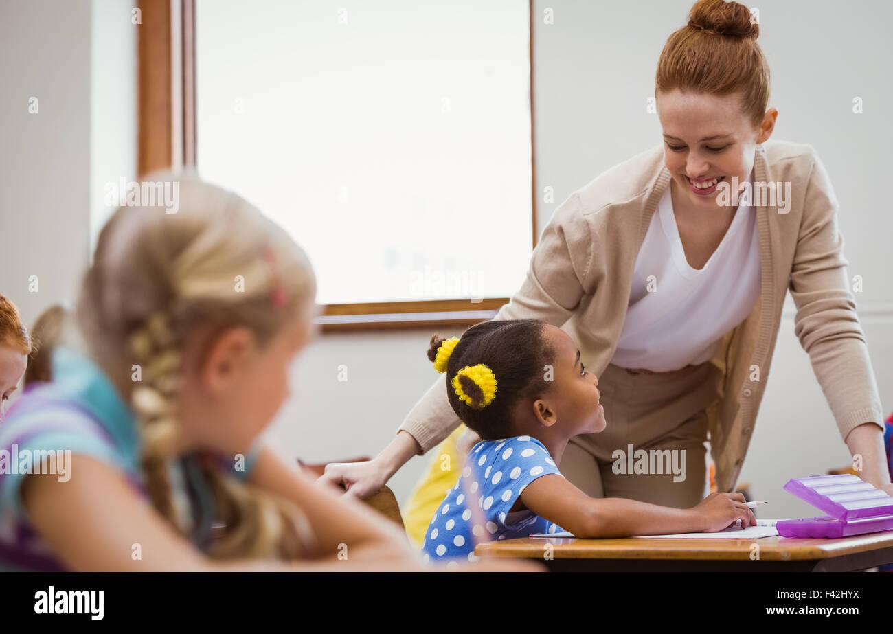 Teacher helping a little girl during class - Stock Image