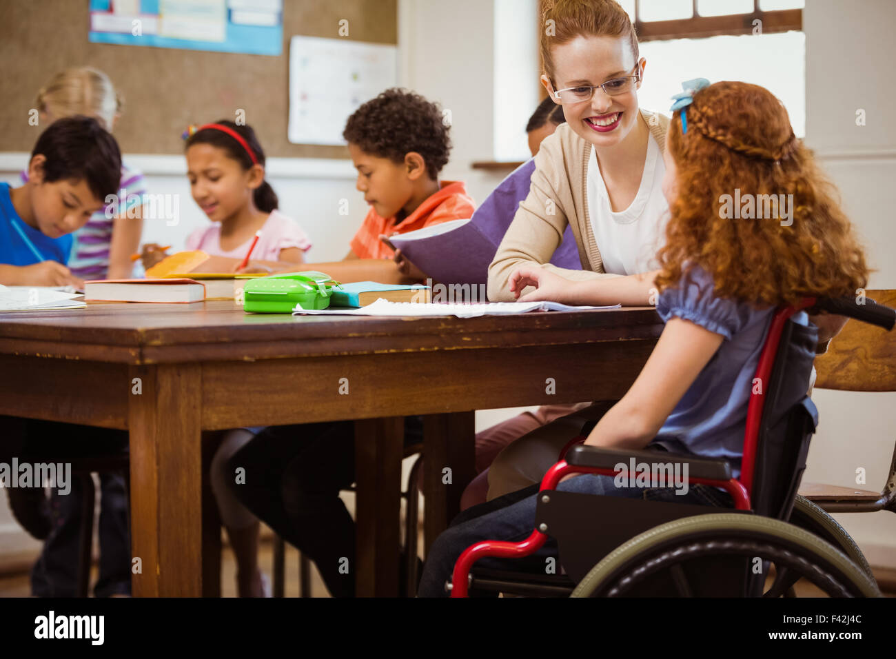 Teacher helping a disabled pupil - Stock Image