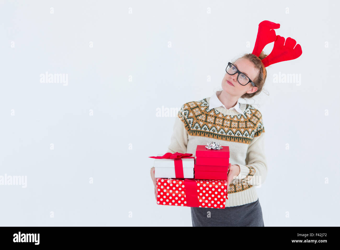 Thoughtful geeky hipster holding presents - Stock Image