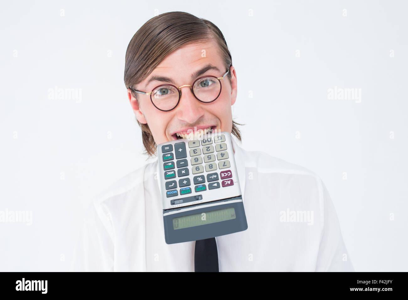 Geeky smiling businessman biting calculator - Stock Image
