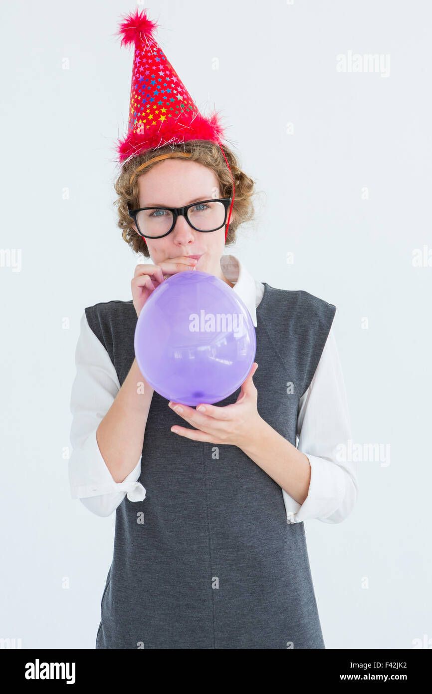 Geeky hipster blowing up balloon - Stock Image