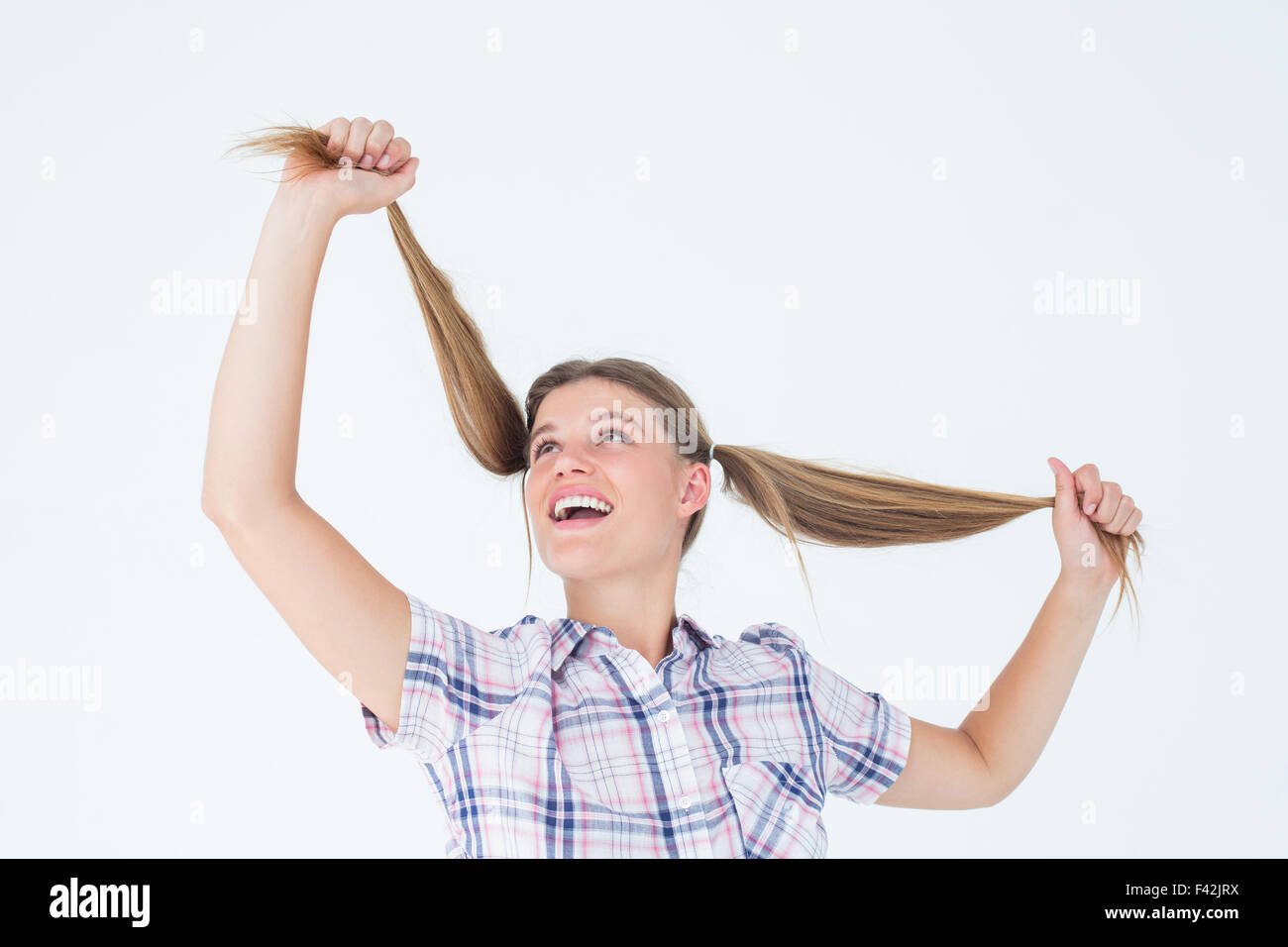 Geeky hipster holding her pigtails - Stock Image