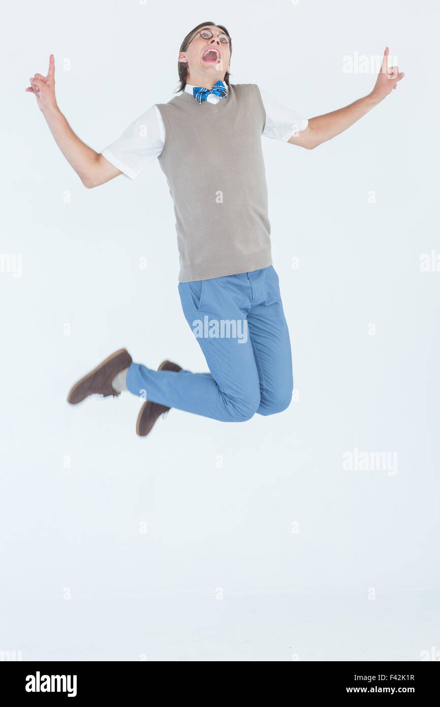 Geeky hipster jumping and smiling - Stock Image