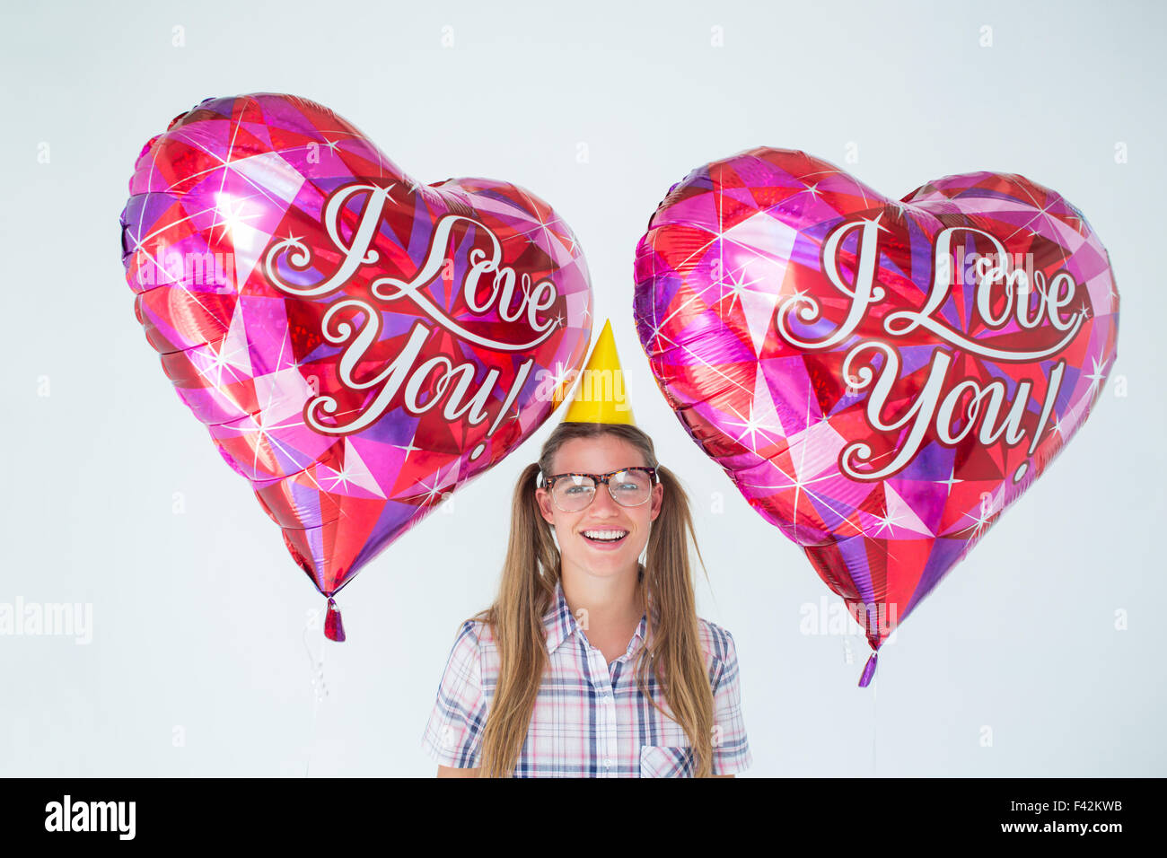 Geeky hipster holding balloons - Stock Image