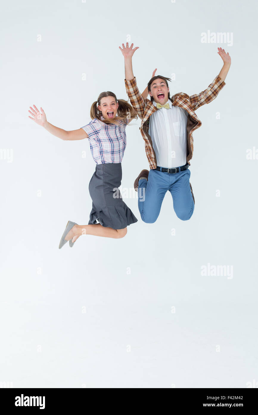 Geeky hipsters jumping and smiling - Stock Image