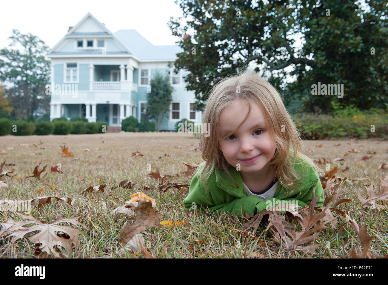 Girl lying on stomach on lawn, smiling, portrait - Stock Image