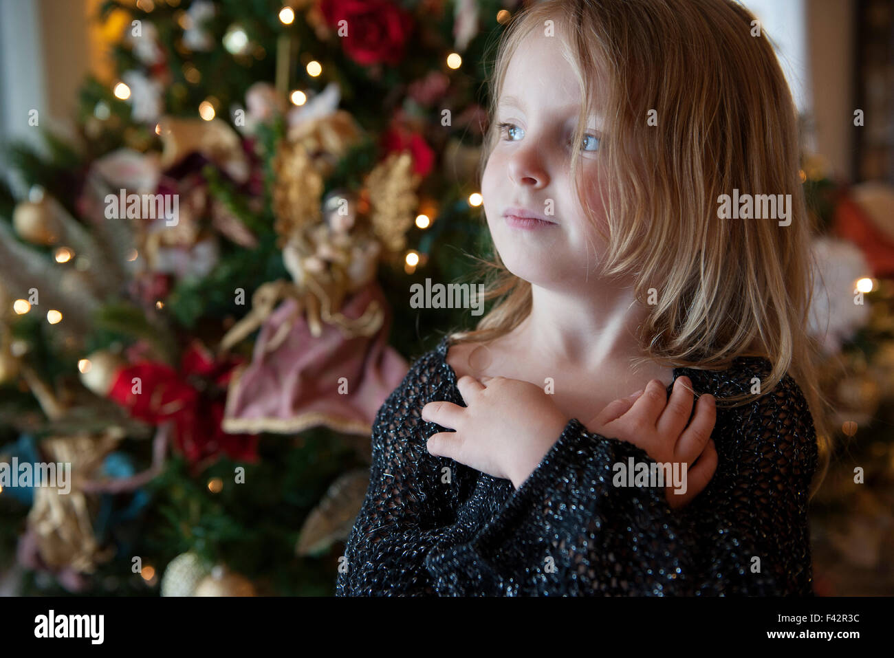 Girl daydreaming with Christmas tree in background - Stock Image
