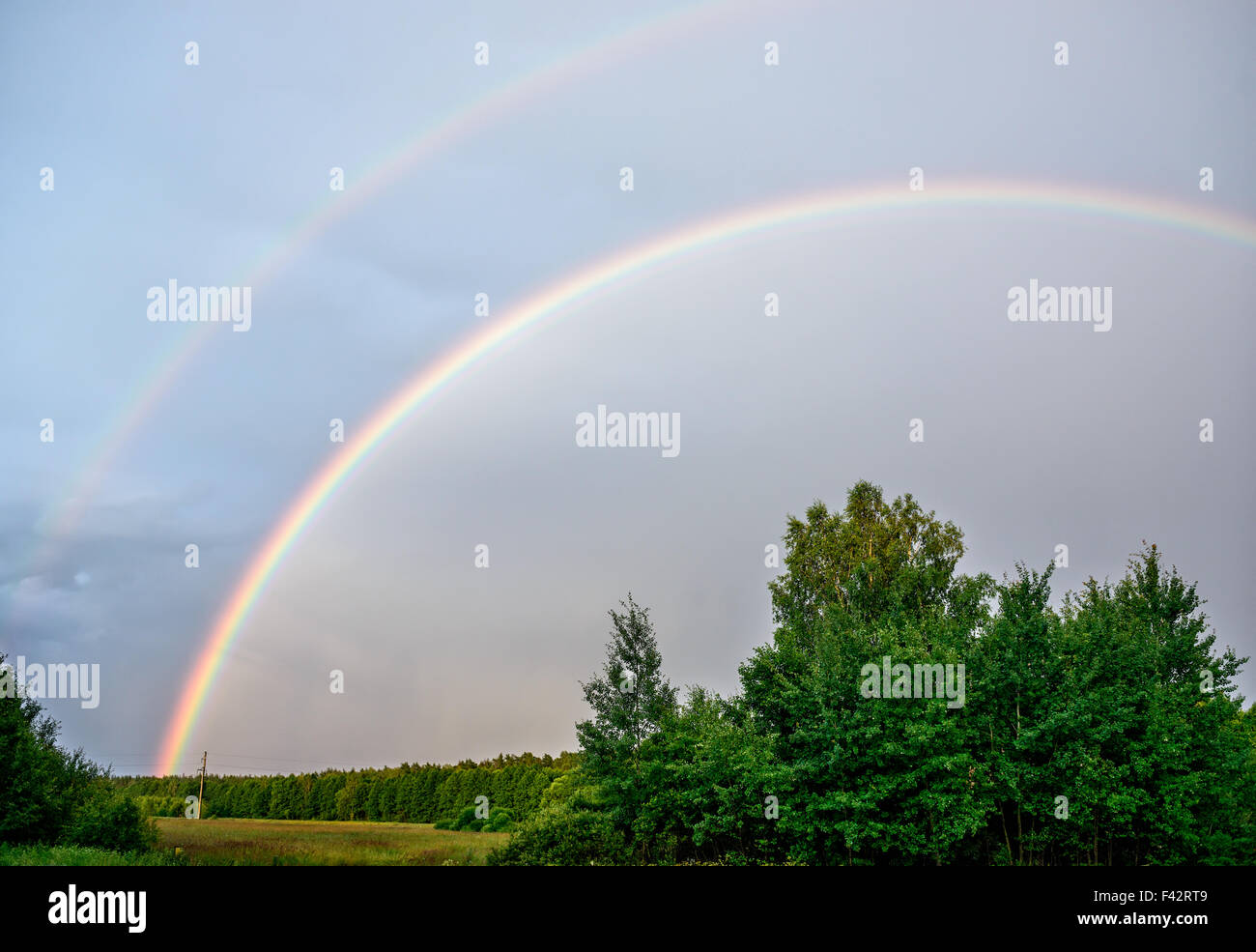 Cloudy sky with rainbows - Stock Image