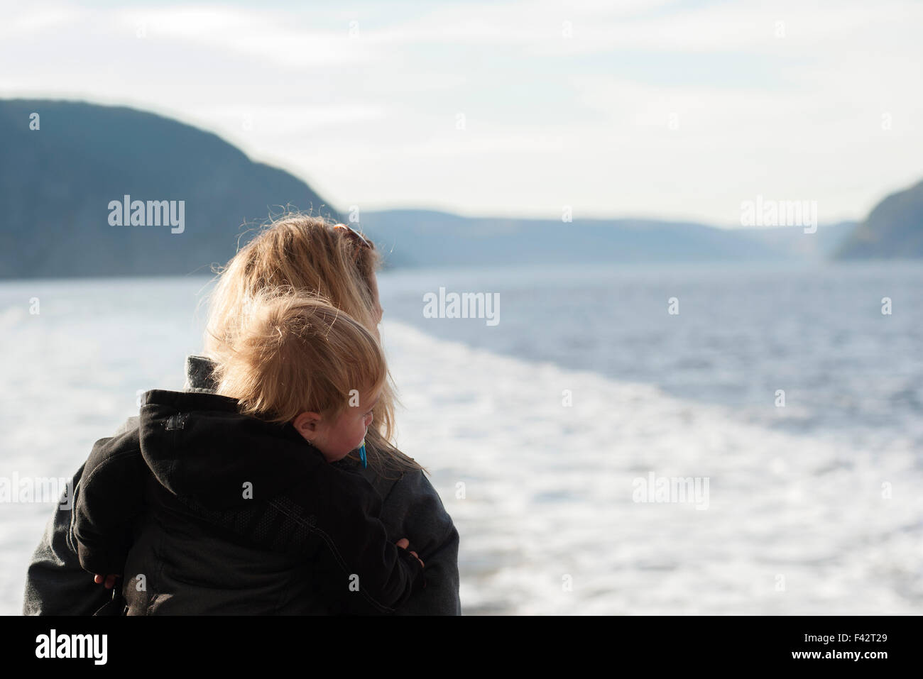 Mother and young son looking at tranquil lake view - Stock Image