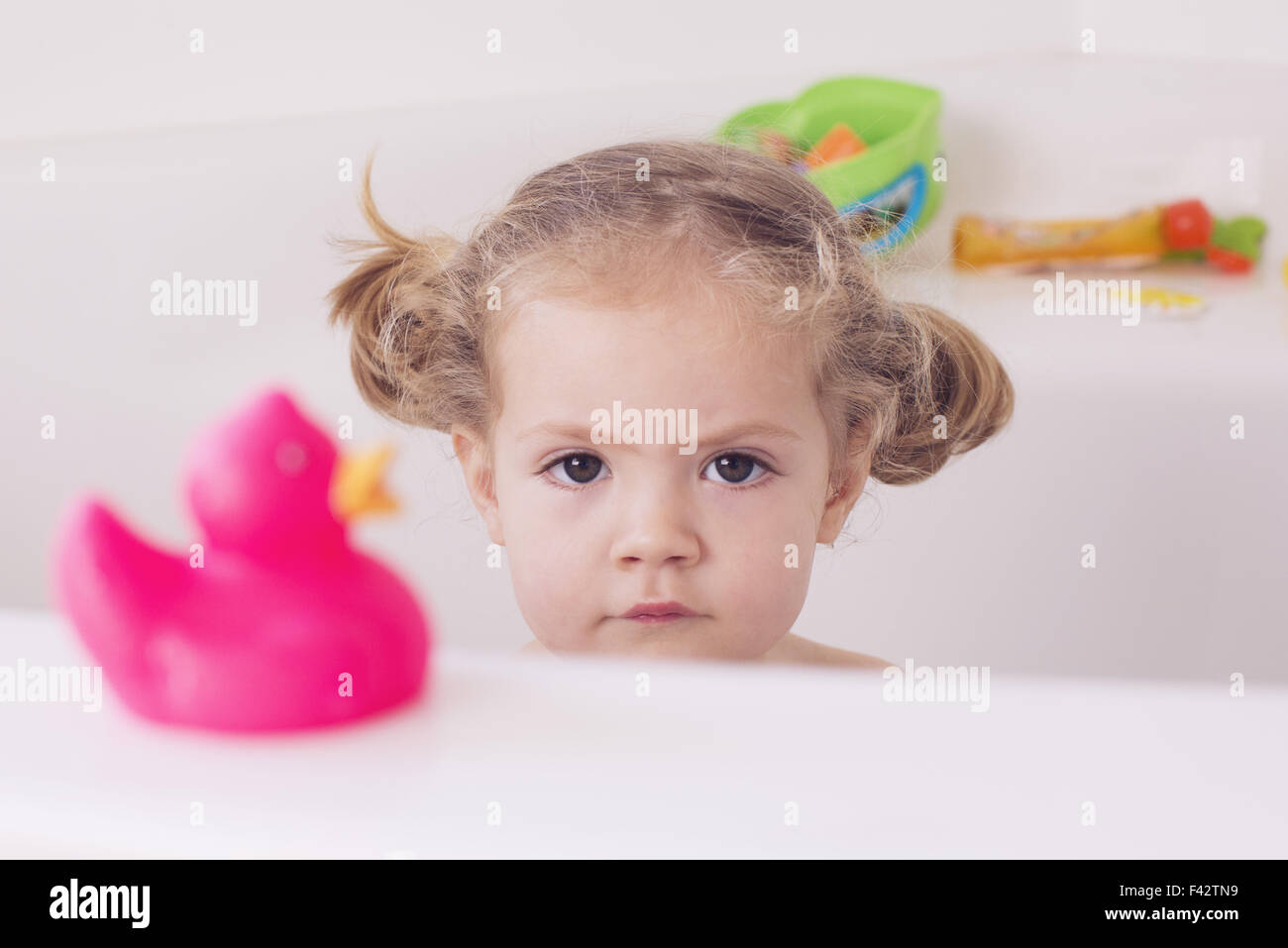Little girl sitting in bath with unhappy expression, portrait - Stock Image