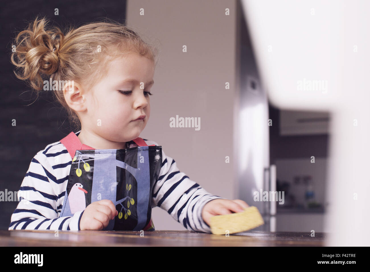 Little girl wiping table with spong - Stock Image