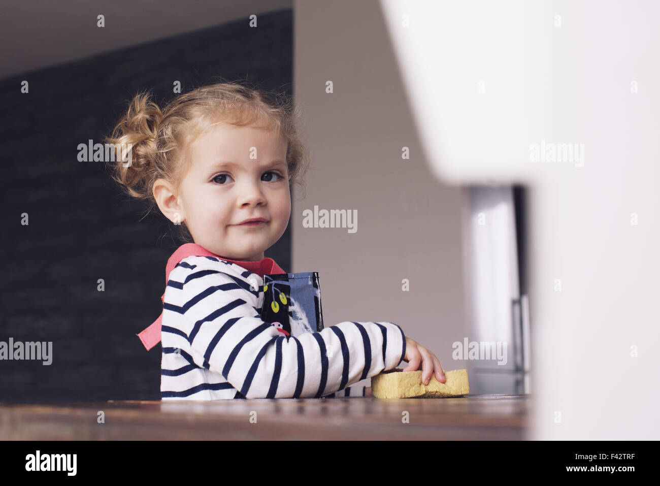 Little girl helping with housework, portrait - Stock Image