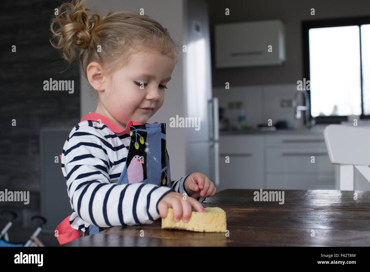 Little girl wiping table with sponge - Stock Image
