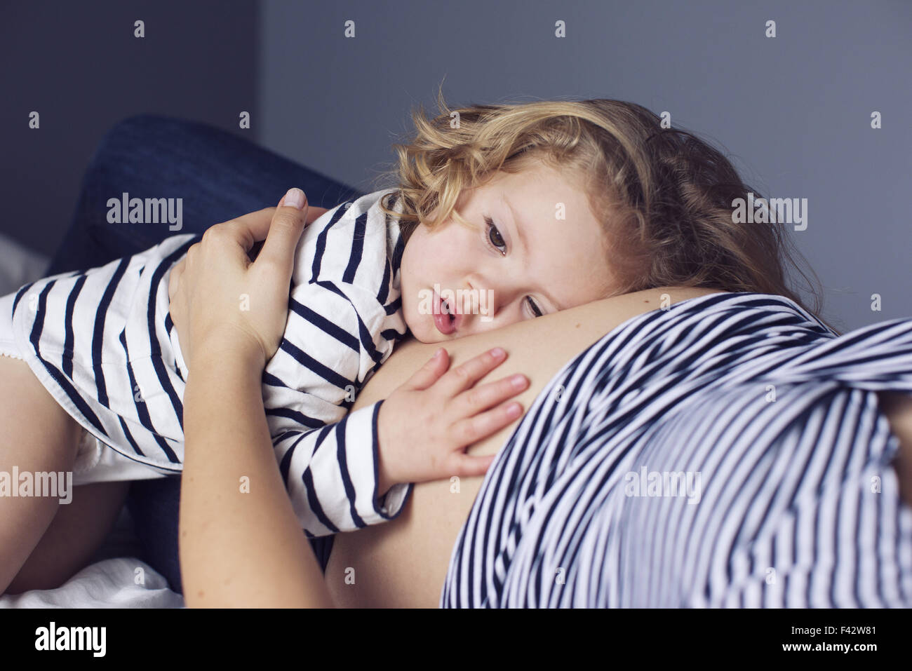 Little girl resting her head and hand on mother's pregnant stomach - Stock Image
