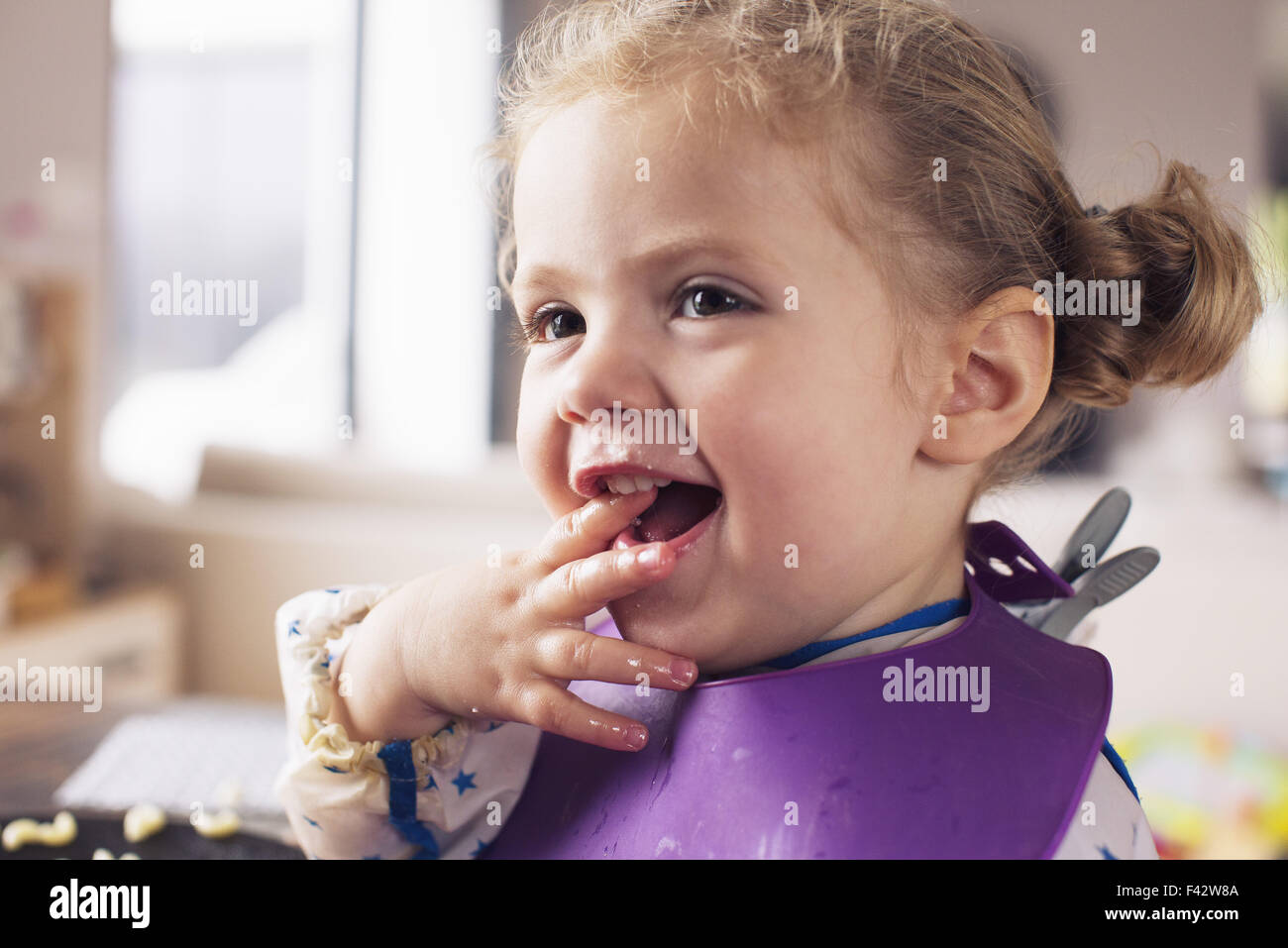 Little girl with fingers in mouth - Stock Image