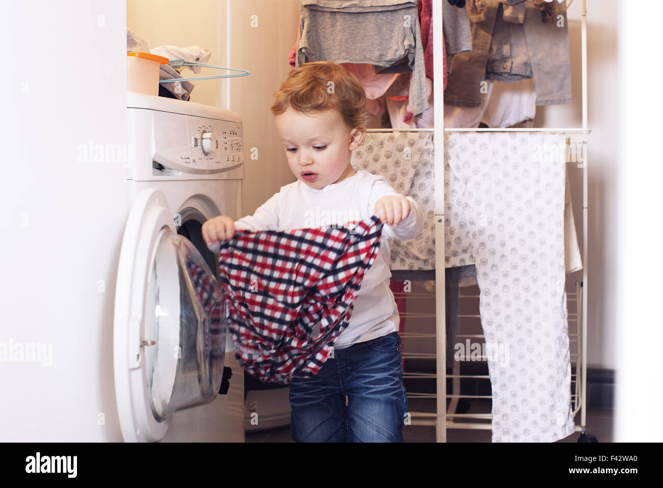 Little boy taking clothes out of dryer - Stock Image