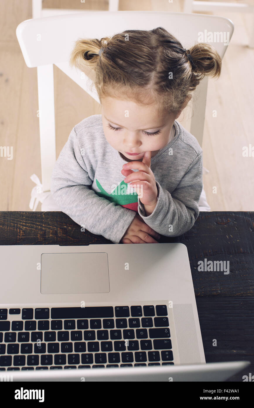 Little girl looking at laptop computer - Stock Image