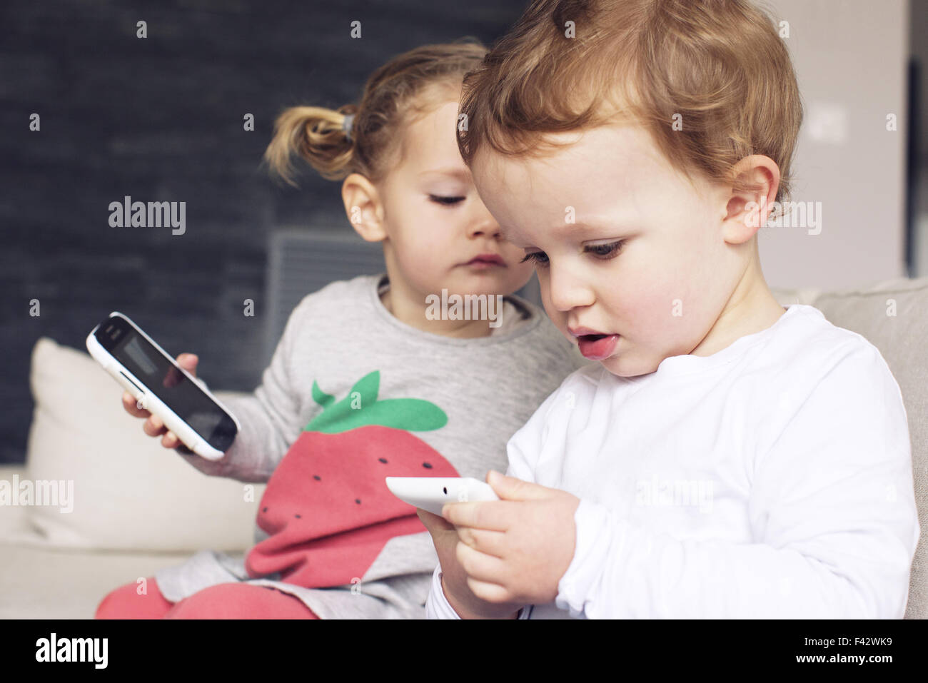 Children playing with smartphones - Stock Image