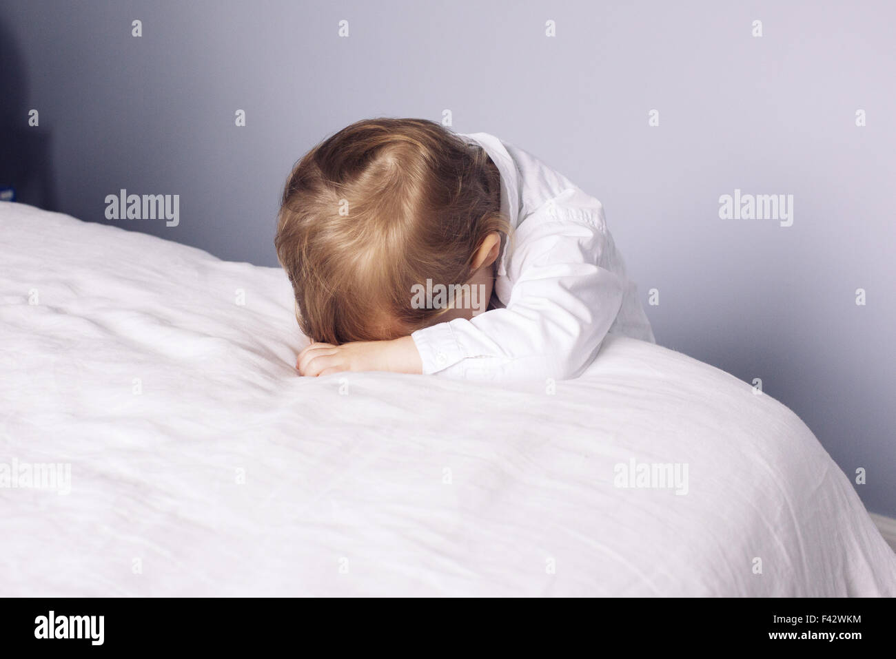 Little boy resting head on bed - Stock Image