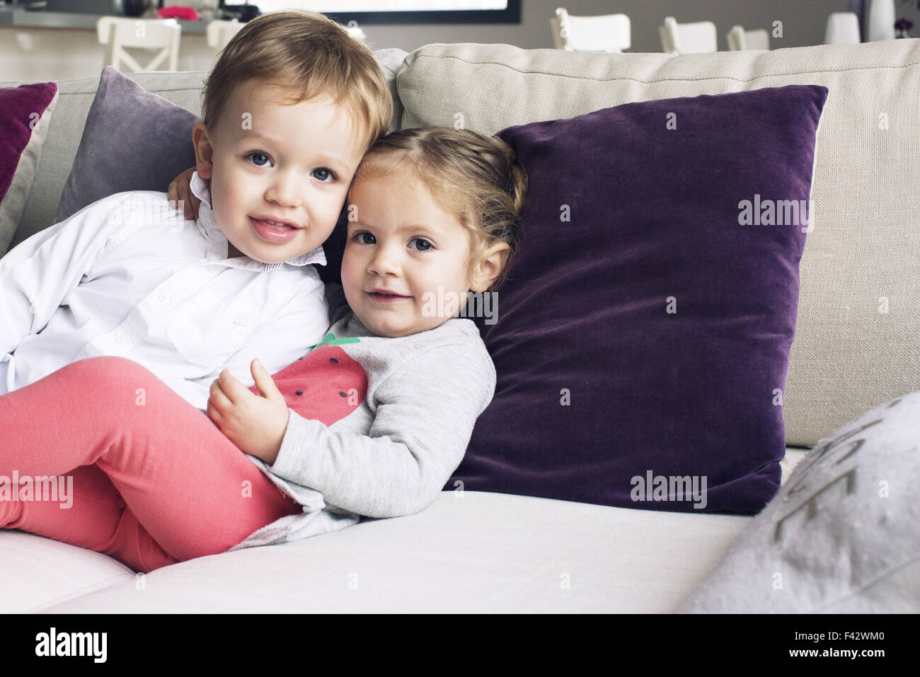 Young siblings sitting together on sofa, portrait Stock Photo