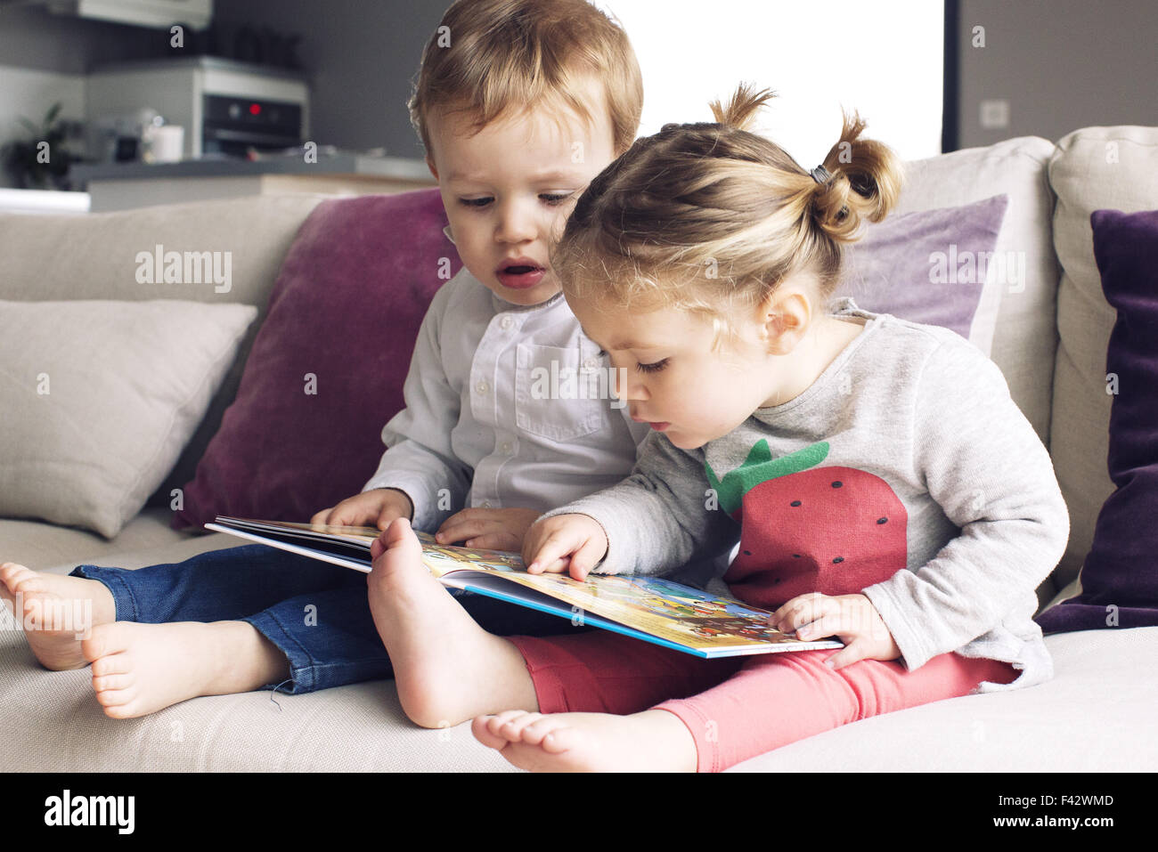 Young siblings looking at book together - Stock Image