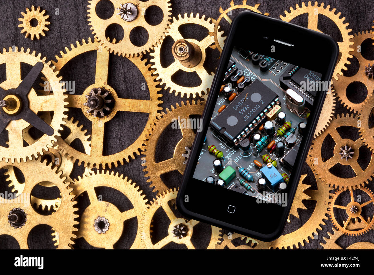 Old and New Technology - Old clockwork cogs and gears and a smartphone with digital technology - Stock Image