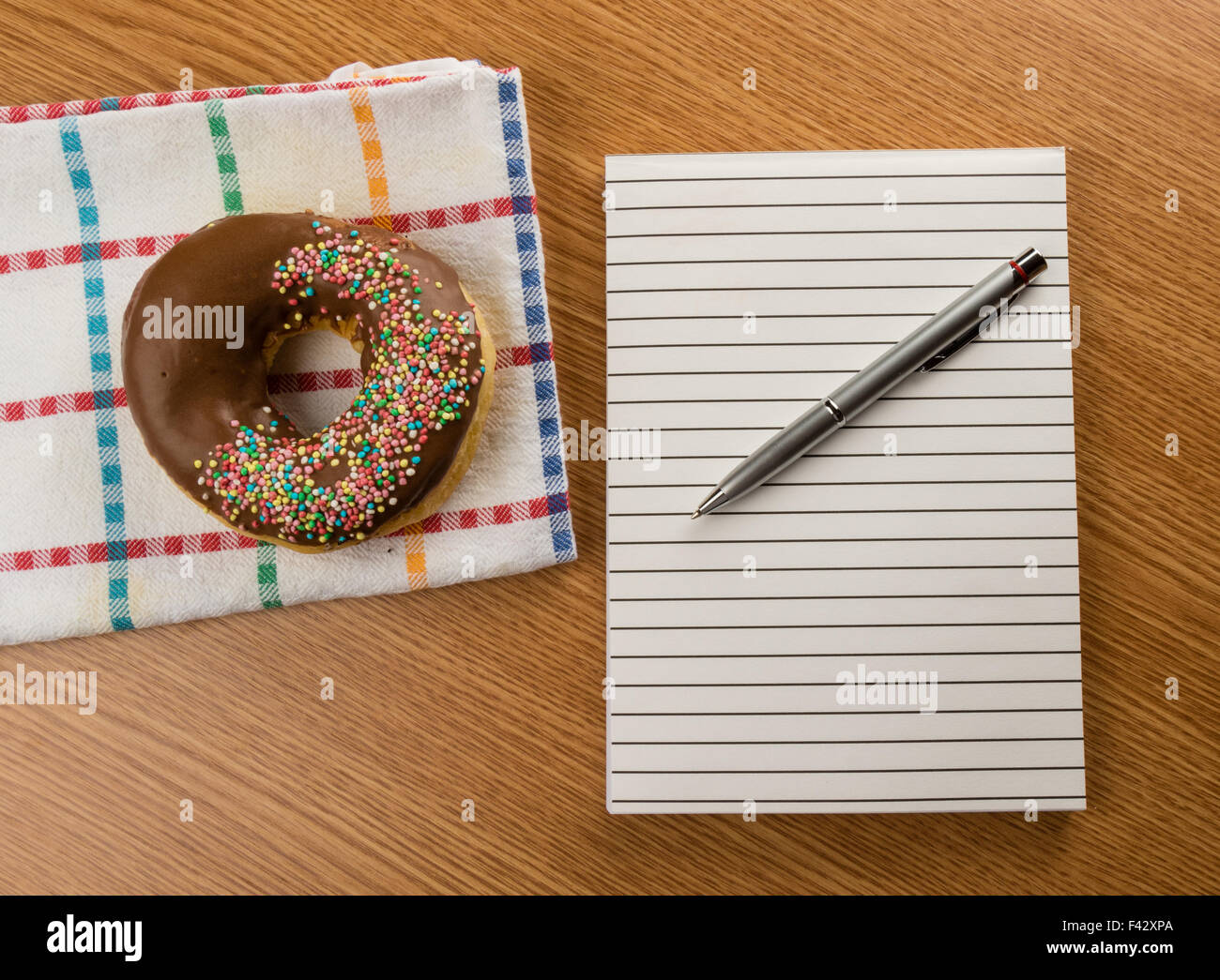 doughnut and notepad with pen - Stock Image