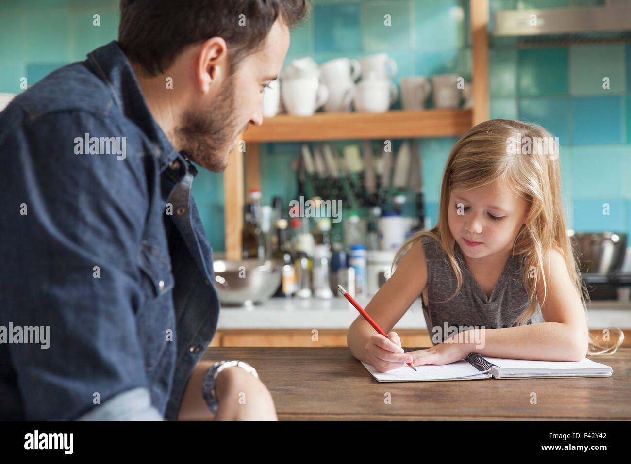 Father helping young daughter with homework - Stock Image