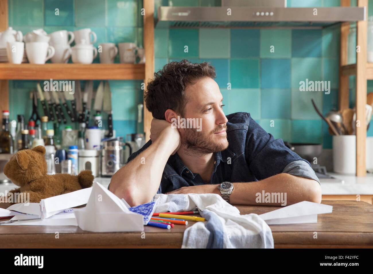 Man daydreaming in kitchen - Stock Image