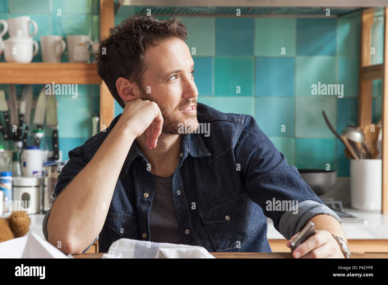 Man daydreaming in messy kitchen - Stock Image
