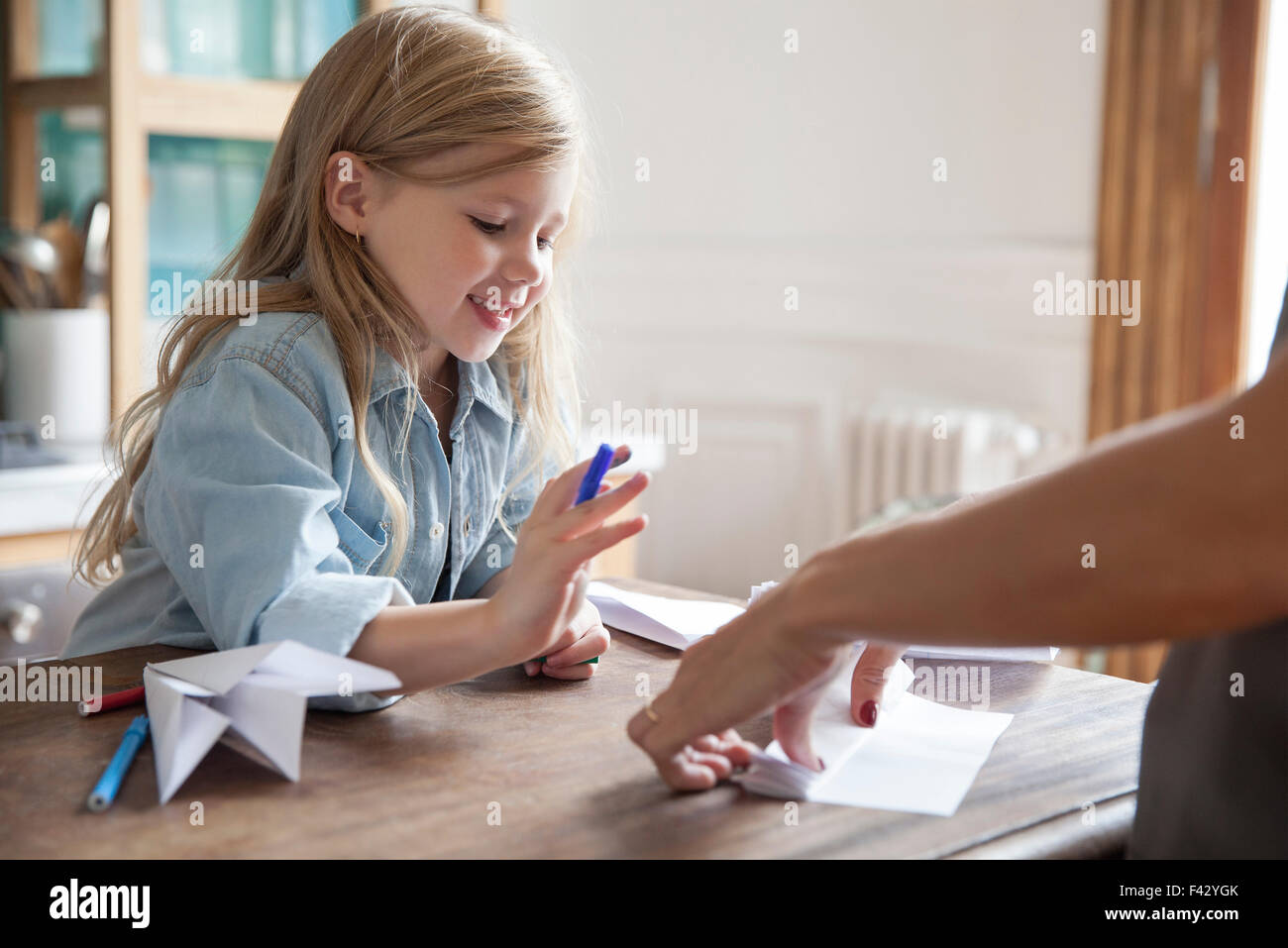 Little girl learning how to make paper airplane - Stock Image