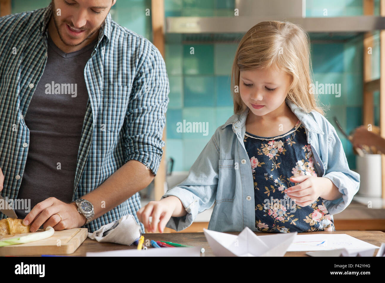 Little girl drawing in kitchen while family prepares meal - Stock Image
