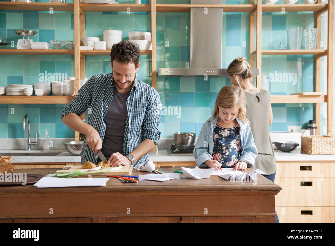 Young daughter drawing ar kitchen counter while parents prepare meal - Stock Image