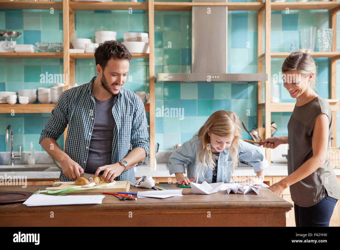 Young daughter drawing at kitchen counter while parents prepare meal - Stock Image