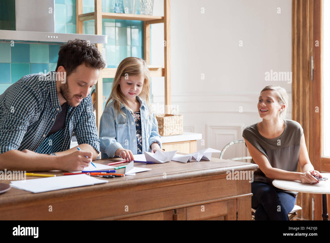 Parents spending time with young daughter at home - Stock Image