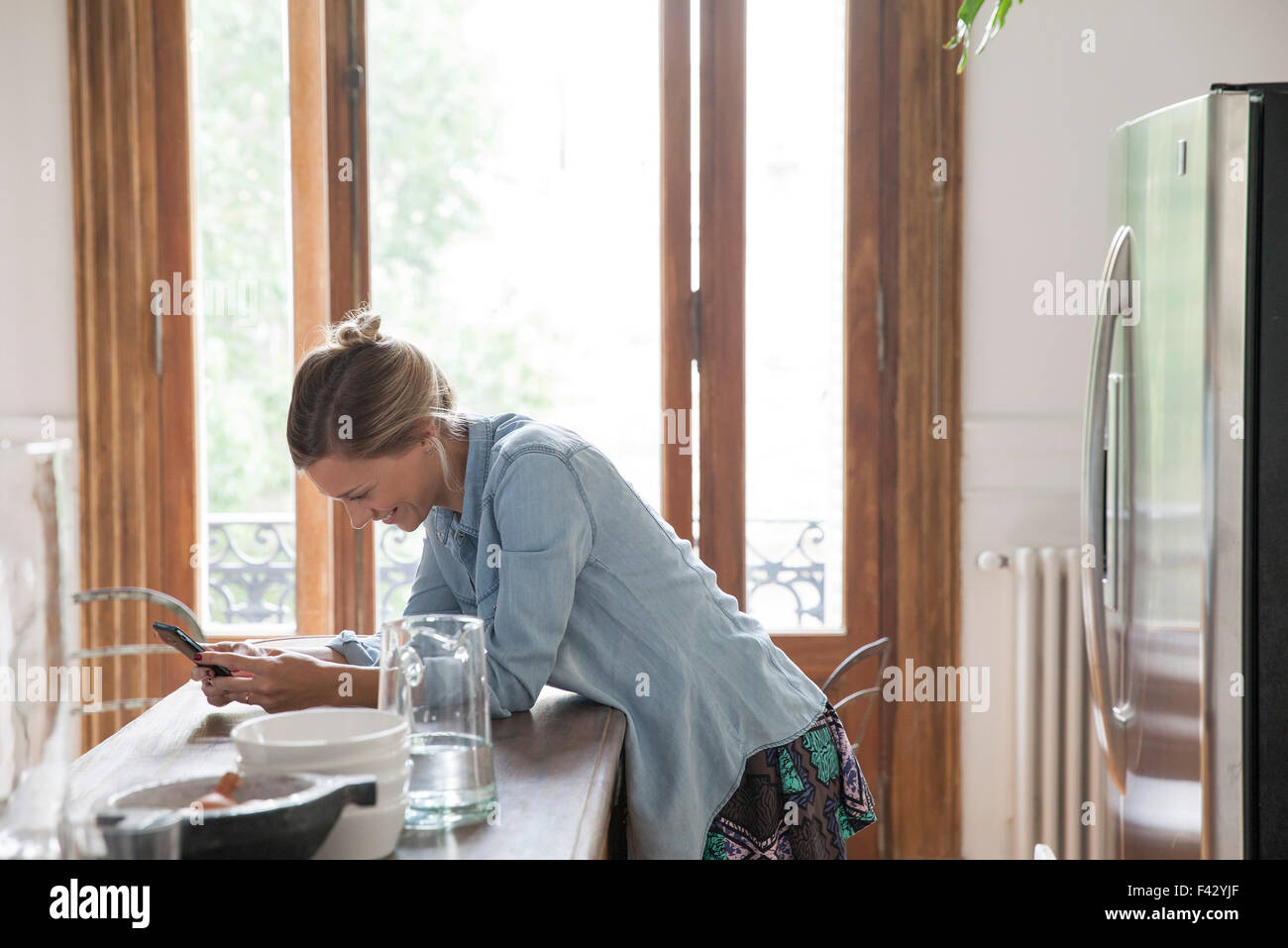 Young woman using smartphone in kitchen - Stock Image