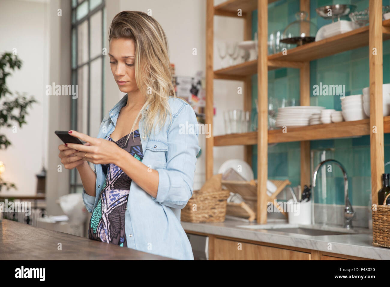 Young woman standing in kitchen with cell phone - Stock Image