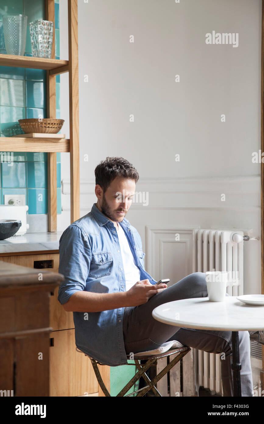 Man sending text message during coffee break - Stock Image