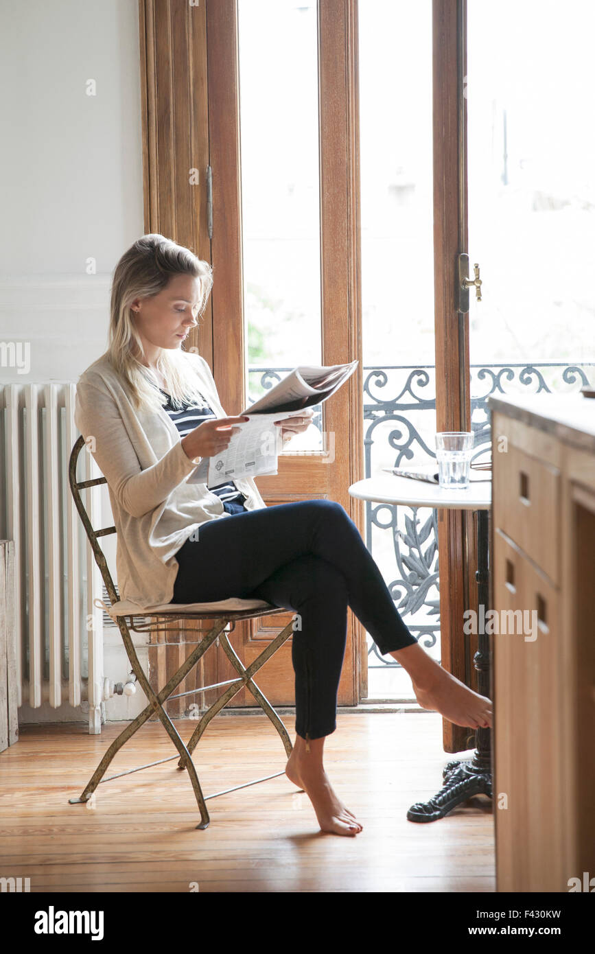 Young woman reading newspaper at home - Stock Image