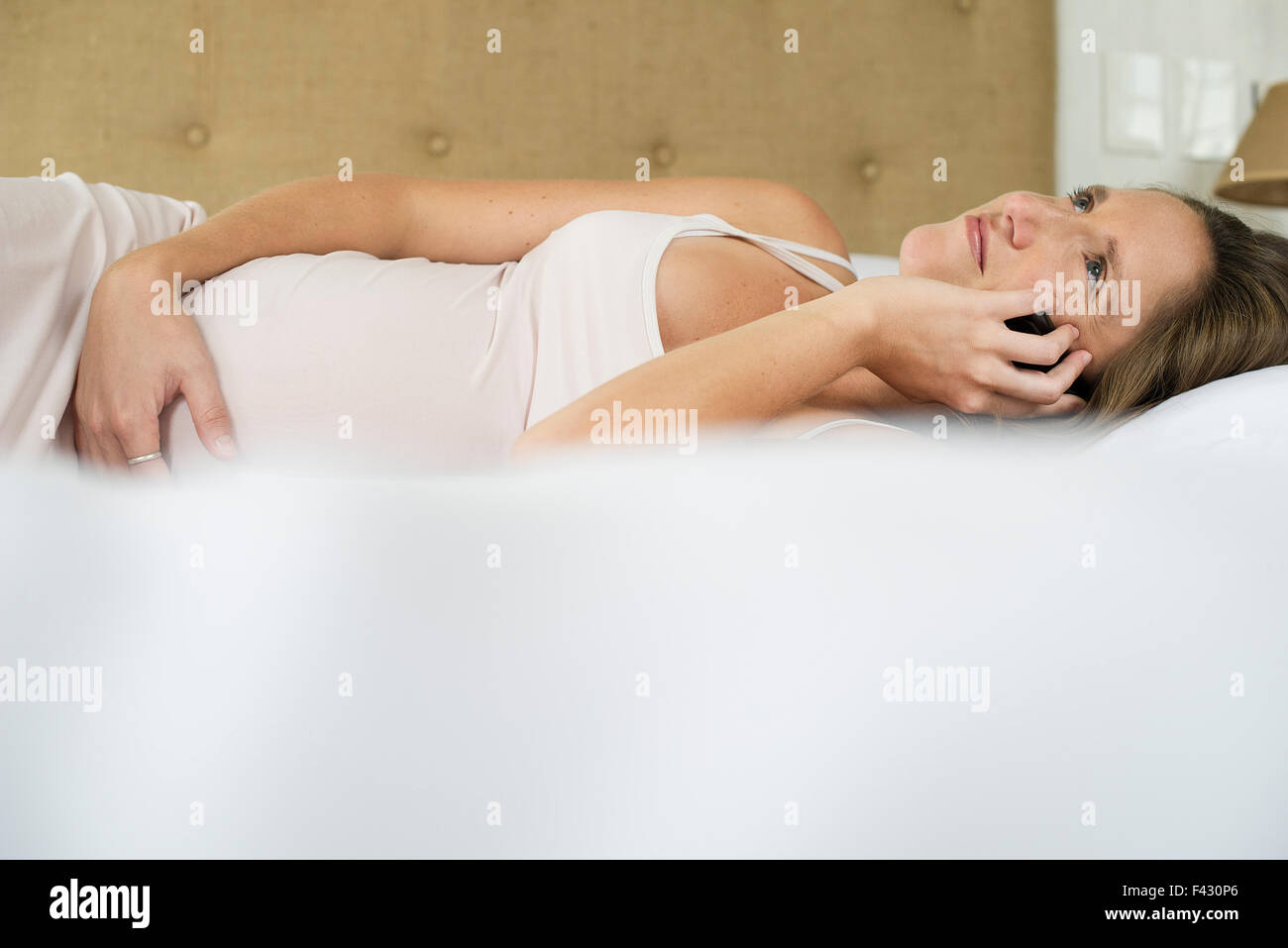 Pregnant woman using cell phone to stay in touch with friends and family - Stock Image