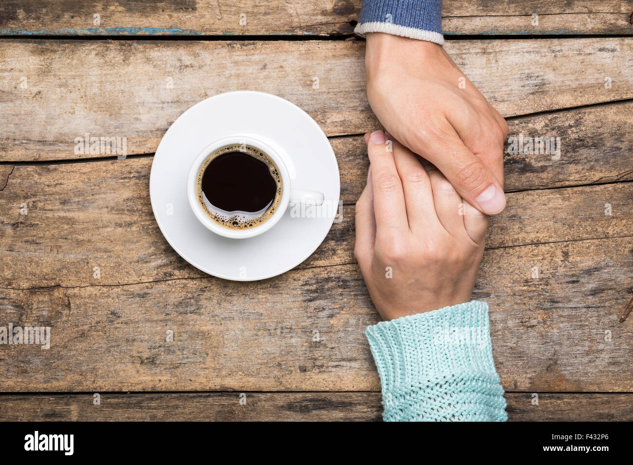 Man holds woman's hand with cup of coffee top view image on wooden backdrop. Friendship coffee background - Stock Image