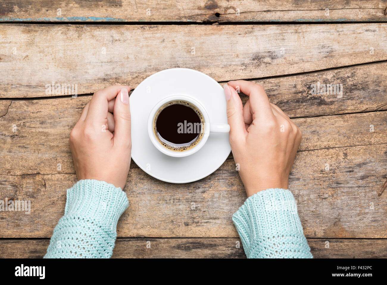 Woman holding cup of espresso on wooden table. Breakfast cafe menu background - Stock Image