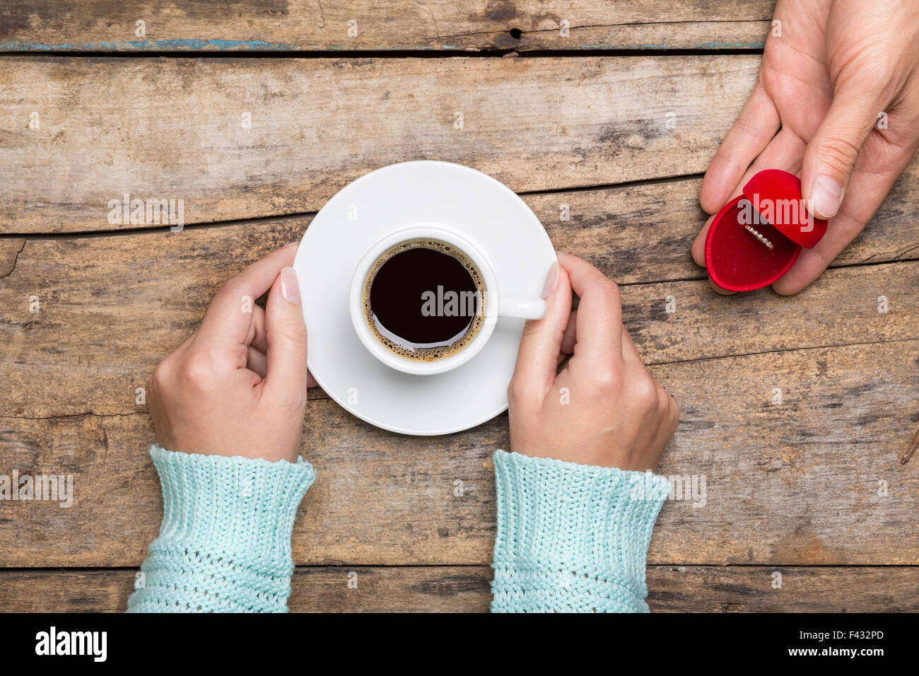Woman holds cup of coffee and man gives gold ring as a gift for birthday or engagement - Stock Image