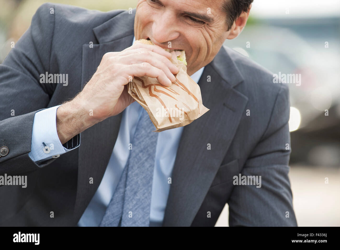 Businessman eating sandwich on the move - Stock Image