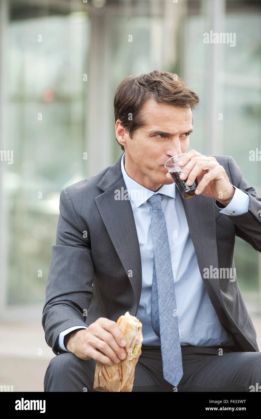 Business executive having lunch outdoors - Stock Image