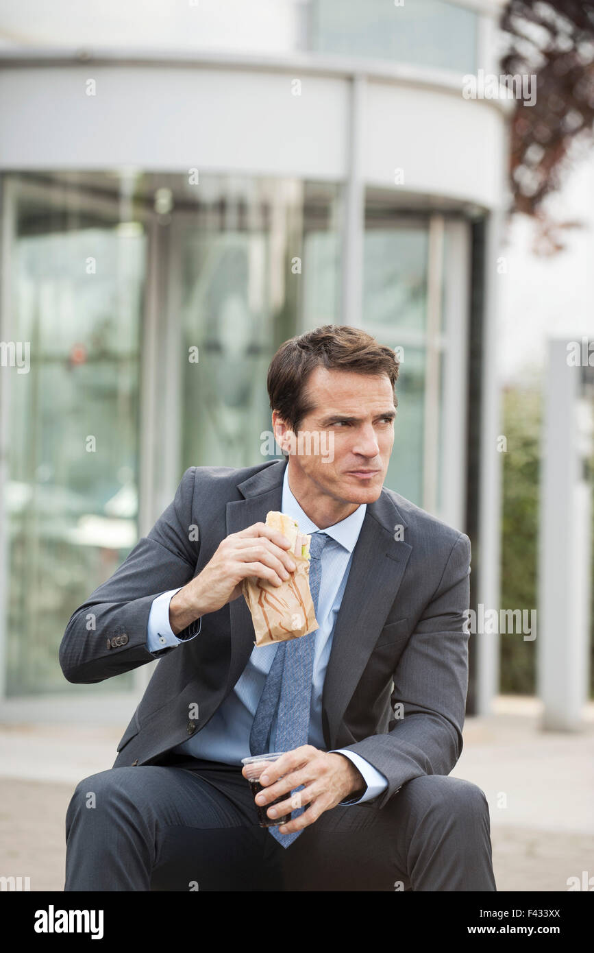 Businessman having lunch outdoors - Stock Image