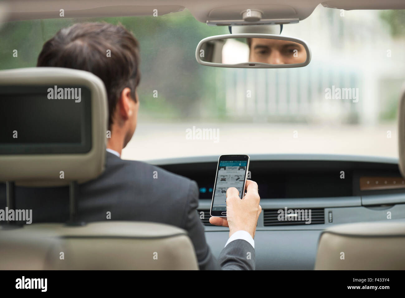 Using cell phone while driving car - Stock Image