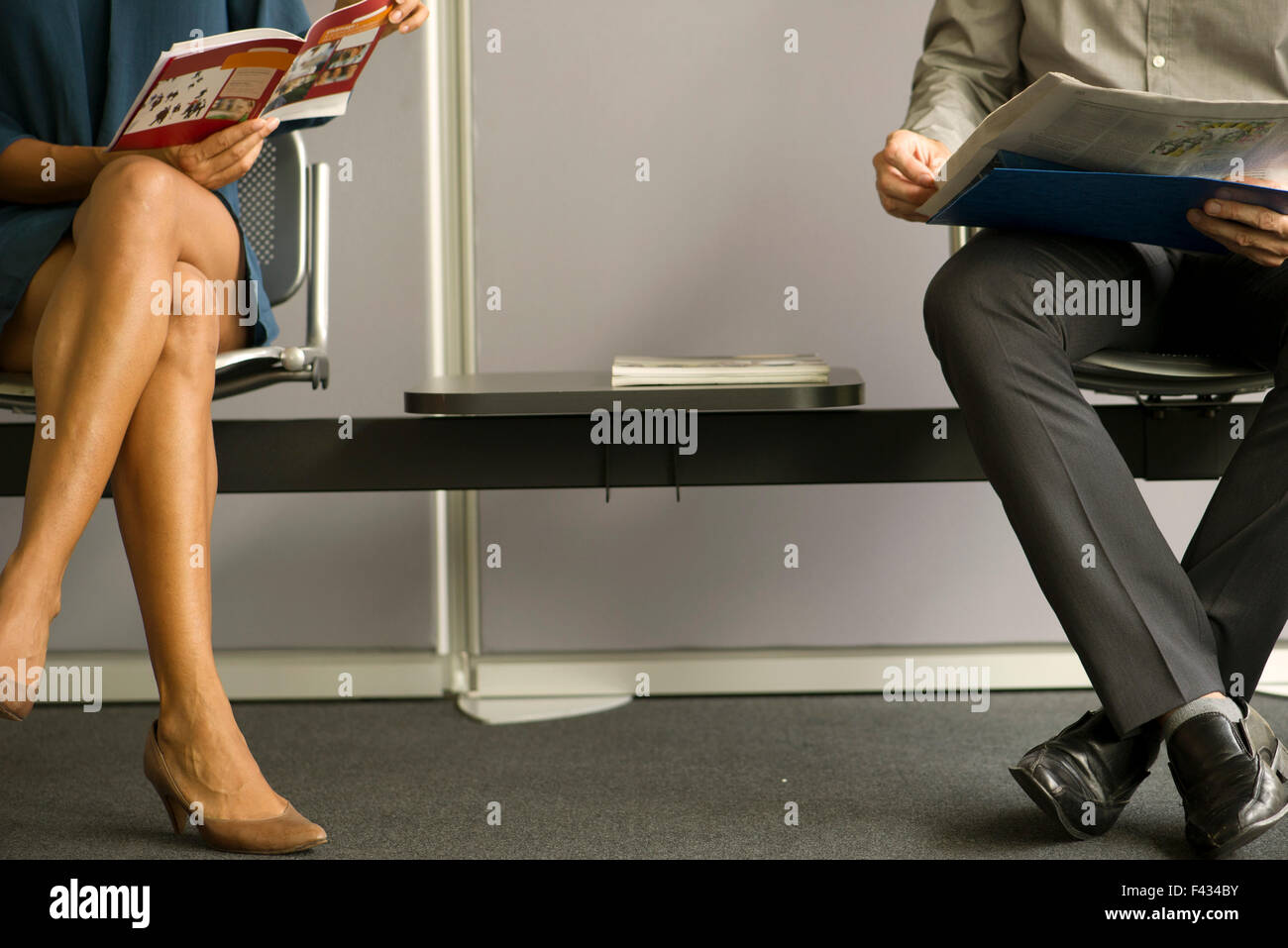 Man and woman sitting in waiting room, low section - Stock Image